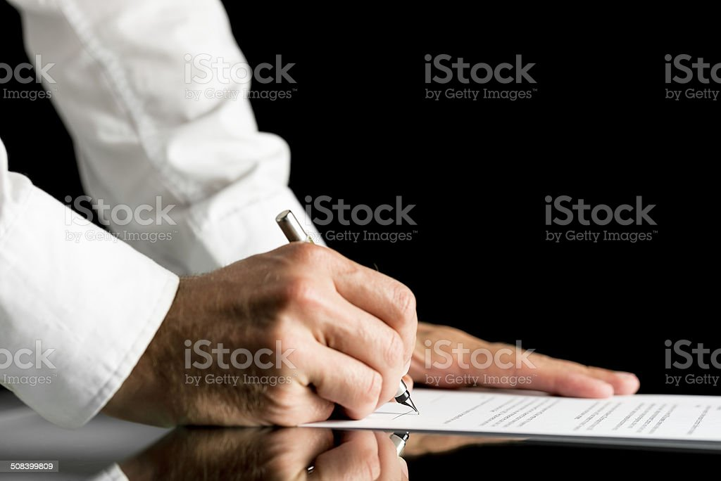 Man signing with a pen an official document stock photo