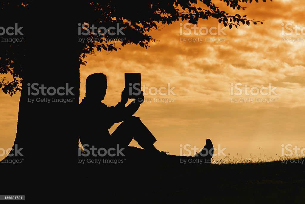 Man silhouette sitting under tree taking photo with tablet outdoor royalty-free stock photo