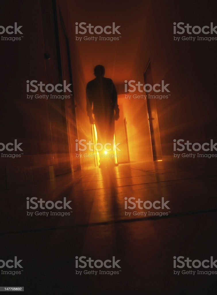 Man silhouette walking in tunnel to the light stock photo