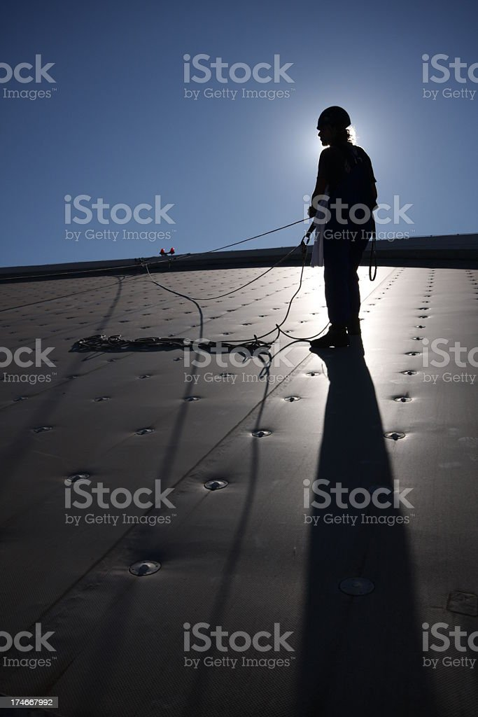 Man silhouetted against sun standing on metal roof royalty-free stock photo