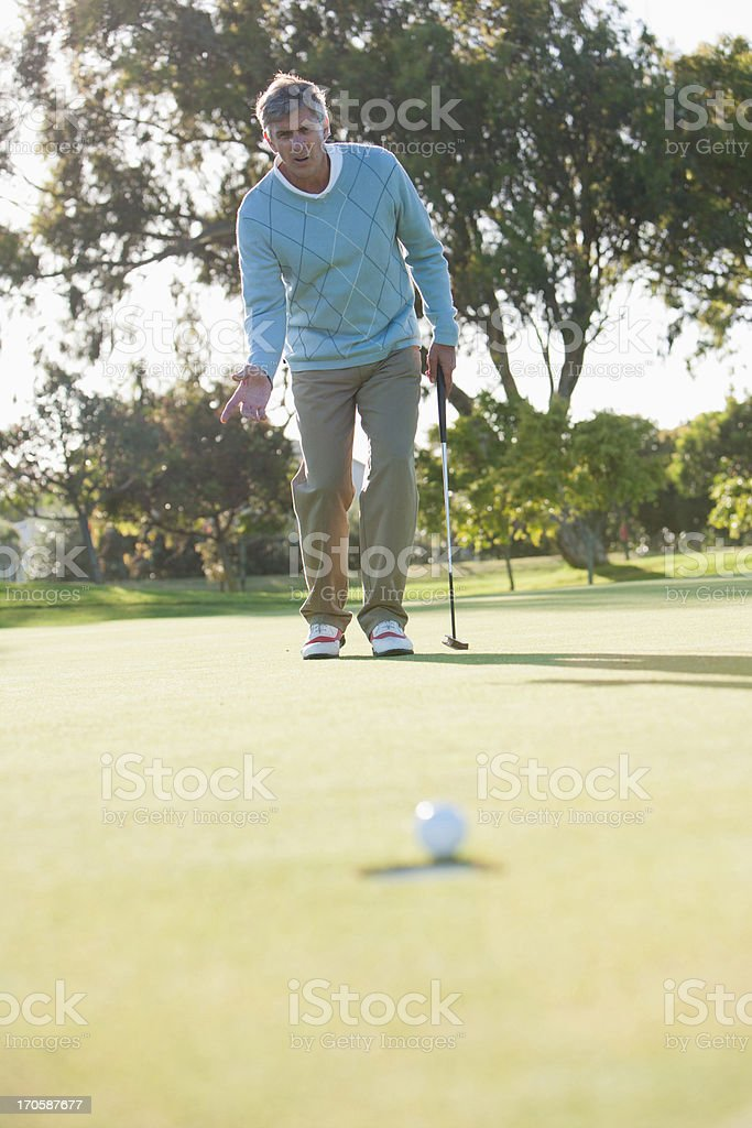 Man sinking golf ball into hole stock photo