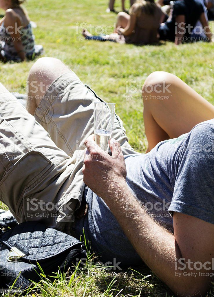 Man sipping champagne at a music festival stock photo