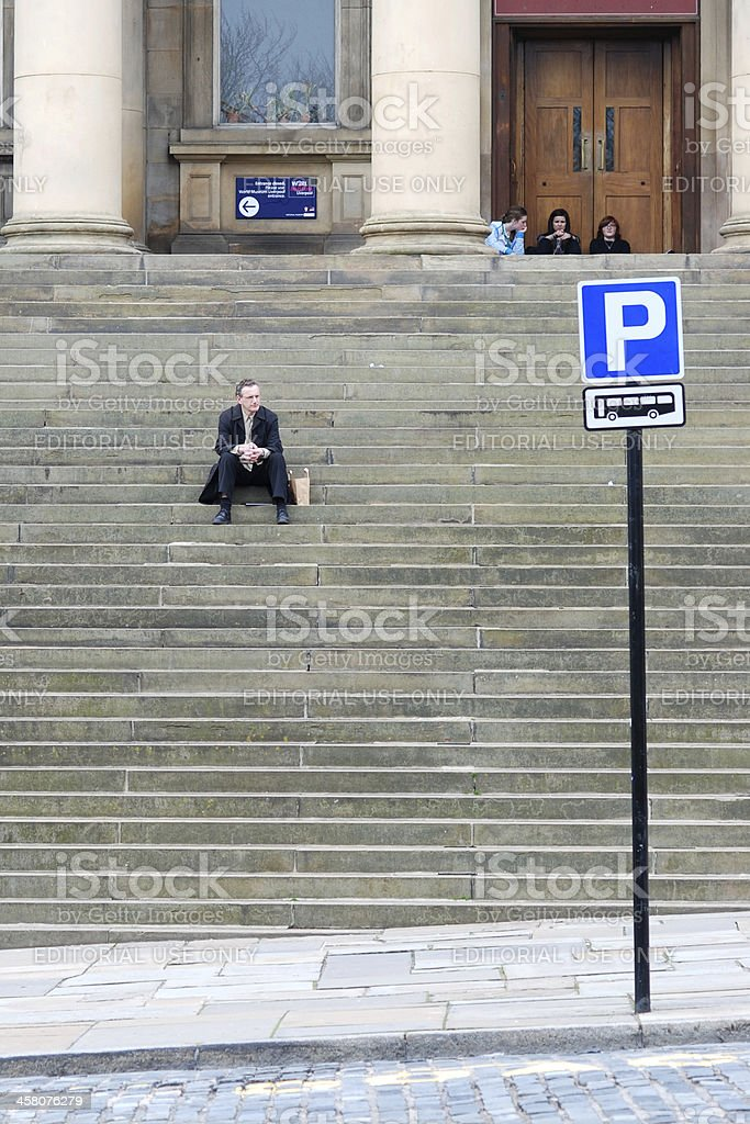 Man sit on staircase in front of Liverpool Central Library stock photo