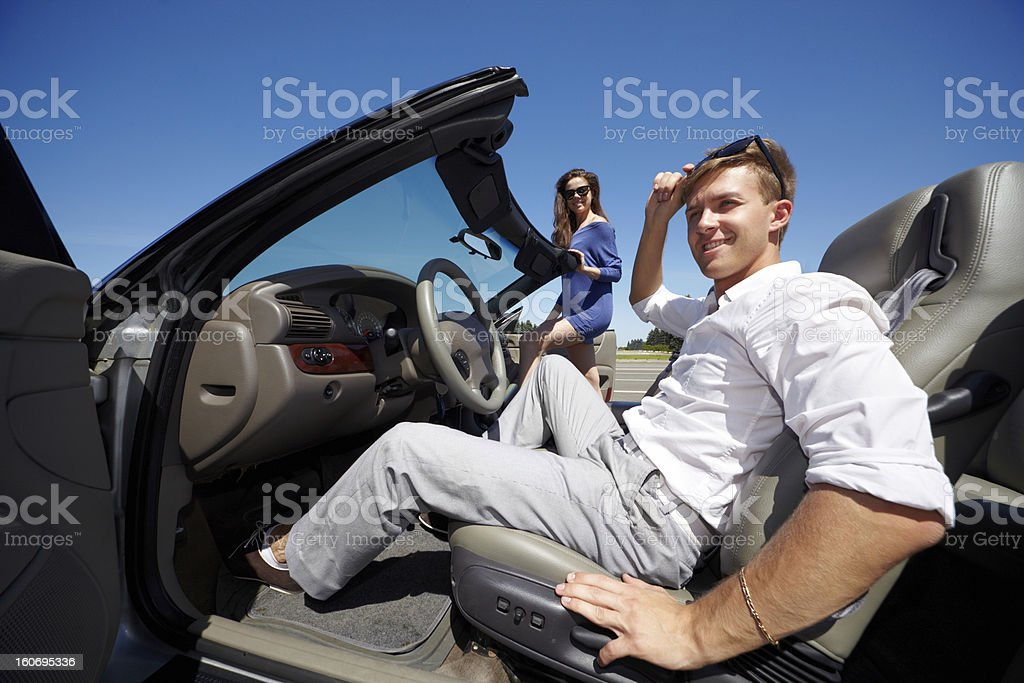 Man sits in cabriolet and his girlfriend gets into car royalty-free stock photo