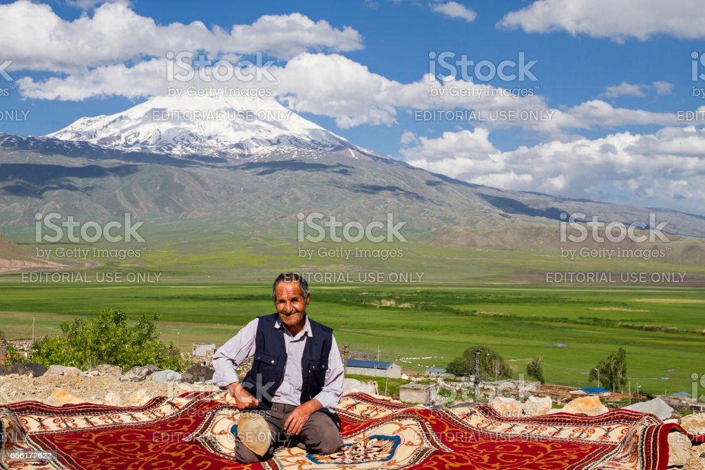 Man sits on a carpet outside, in Dogubayazit, Turkey. Mt Ararat is seen in the background. stock photo