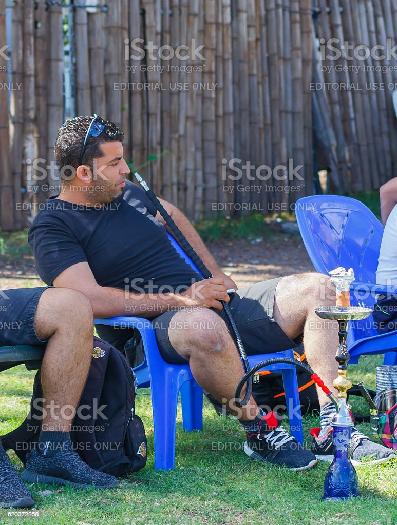 Man sits on a chair and smoking a hookah stock photo