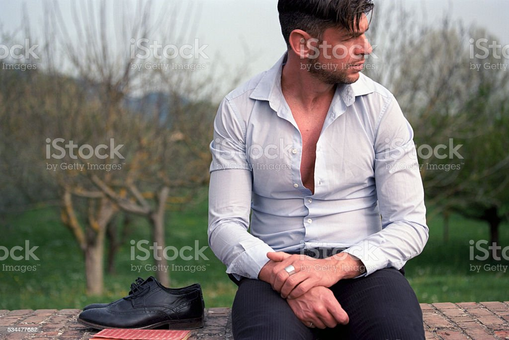 Man sits on a wall in the countryside stock photo