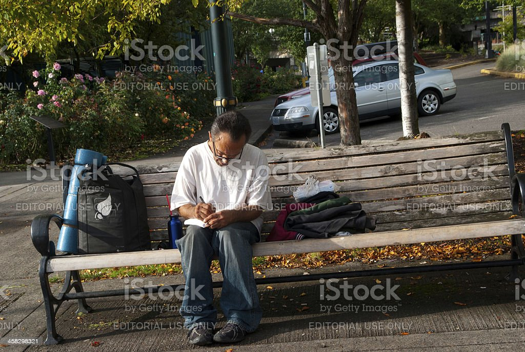 Man sits on bench writing stock photo
