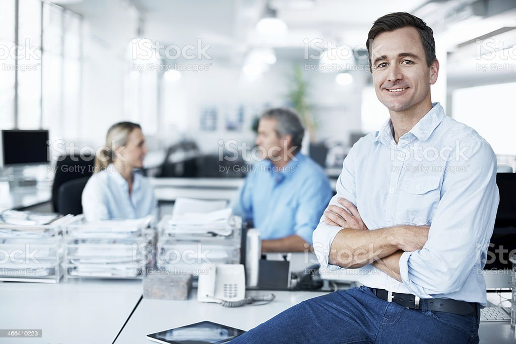 Man sits on desk with arms crossed stock photo