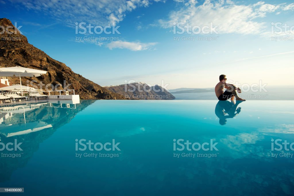 Man Sits On Edge of Infinity Pool Santorini Greece stock photo