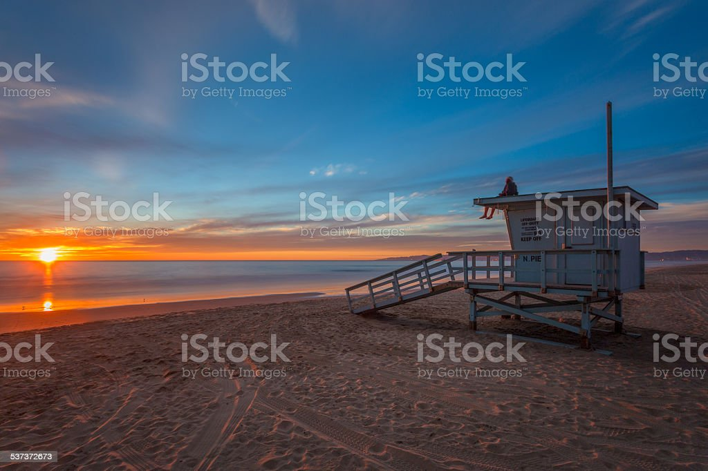 Man sits on lifeguard tower at sunset on beach. stock photo