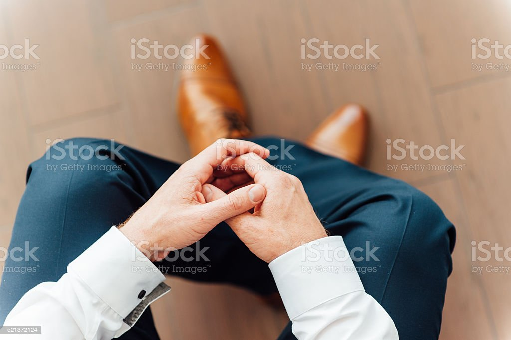 man sits with hands clasped stock photo