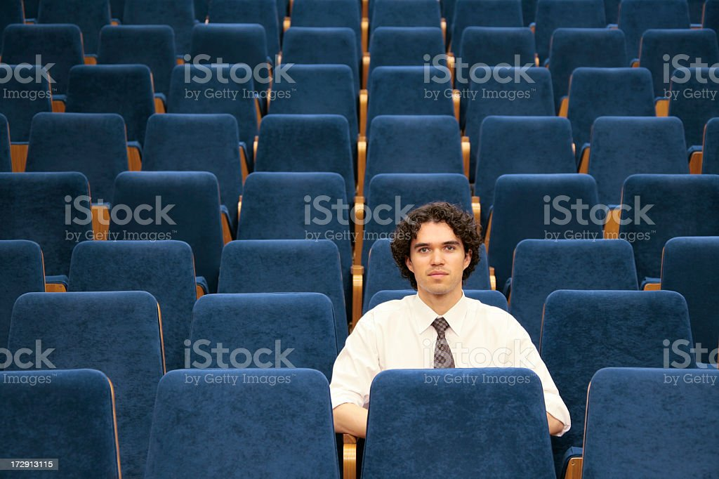 Man sitting alone among empty blue seats in an auditorium royalty-free stock photo