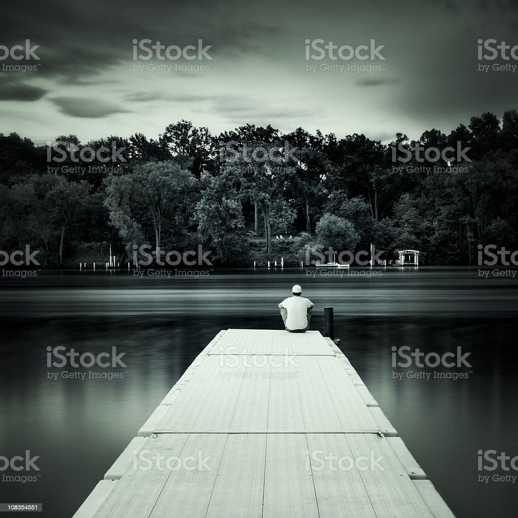 Man sitting alone at the end of a dock royalty-free stock photo