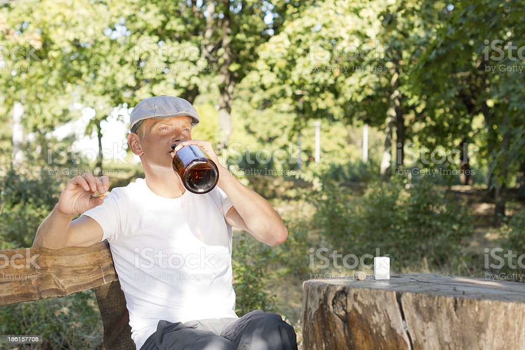 Man sitting alone drinking from a bottle of liquor royalty-free stock photo