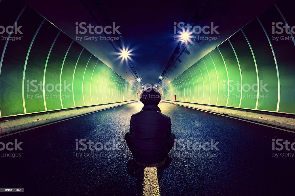 Man Sitting Alone in Middle of a Roadtunnel royalty-free stock photo