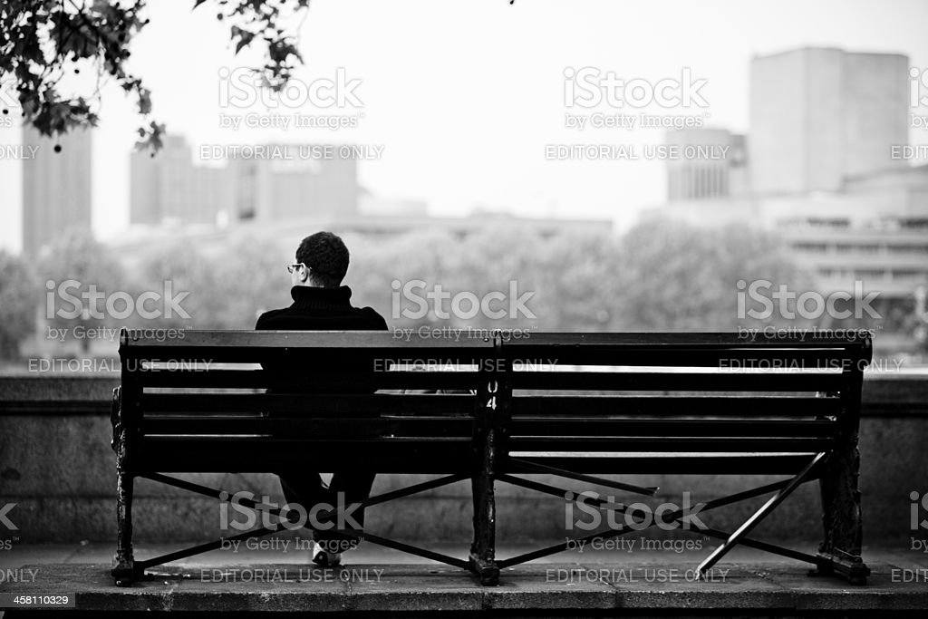 Man sitting alone on a bench staring at IBM building stock photo