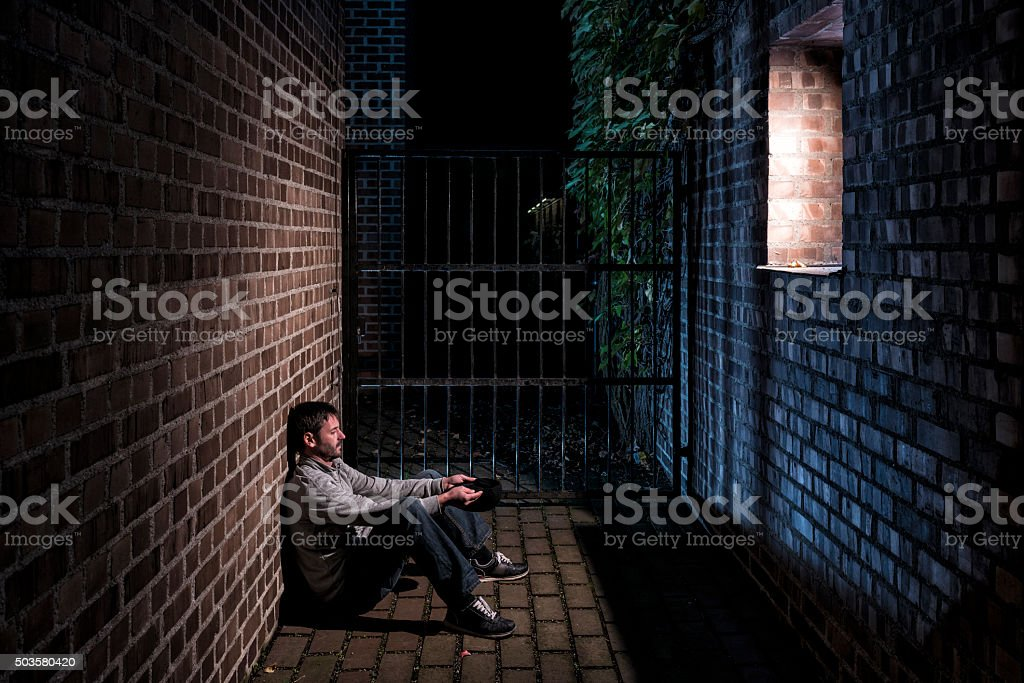 man sitting alone outside at night below window stock photo