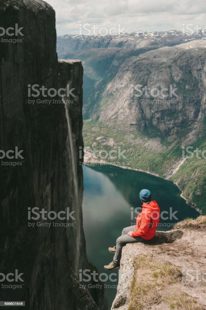 Man sitting and looking at scenic view of Lysefjorden from Kjerag mountain stock photo