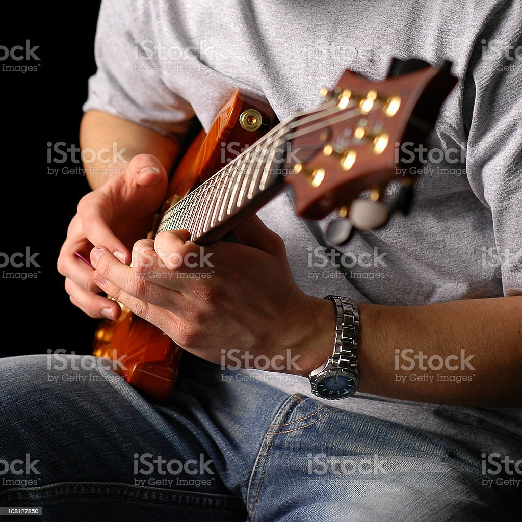 Man Sitting and Playing Electric Guitar, Isolated on Black royalty-free stock photo