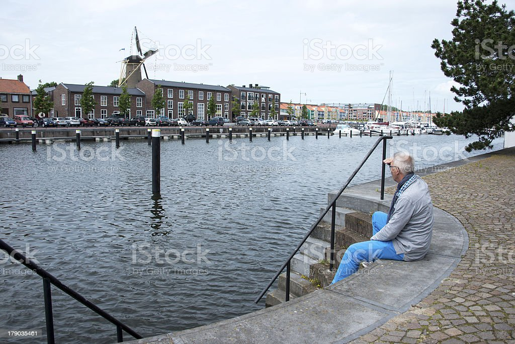 man sitting and thinking near the water royalty-free stock photo