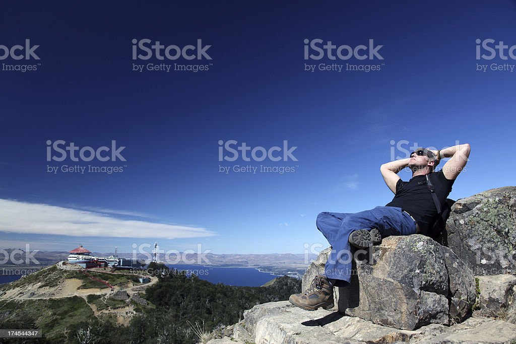 Man Sitting and Thinking on Mountain Summit stock photo