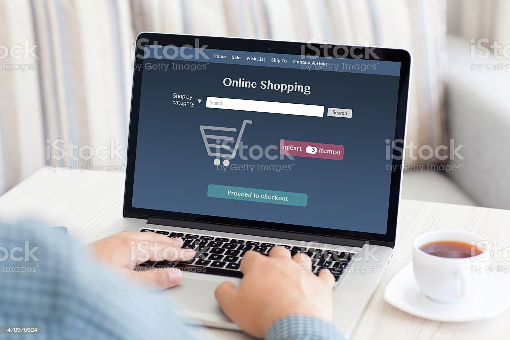 man sitting at a computer and makes online shopping stock photo
