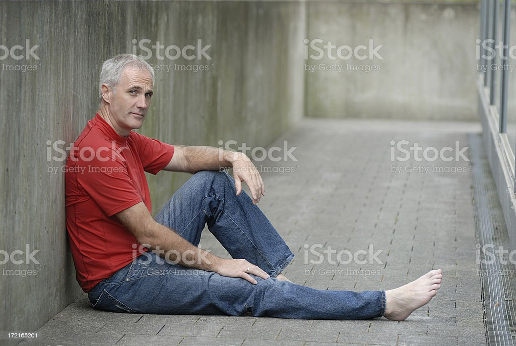 man sitting at a concrete wall royalty-free stock photo