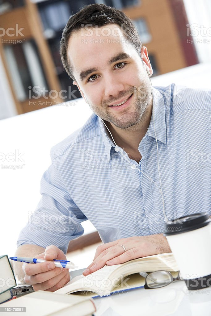 Man Sitting at a Desk Working With Coffee & Book royalty-free stock photo