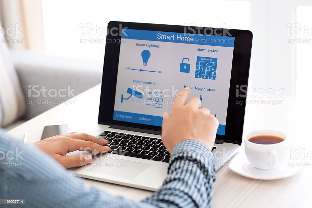 man sitting at a laptop with the program smart home stock photo
