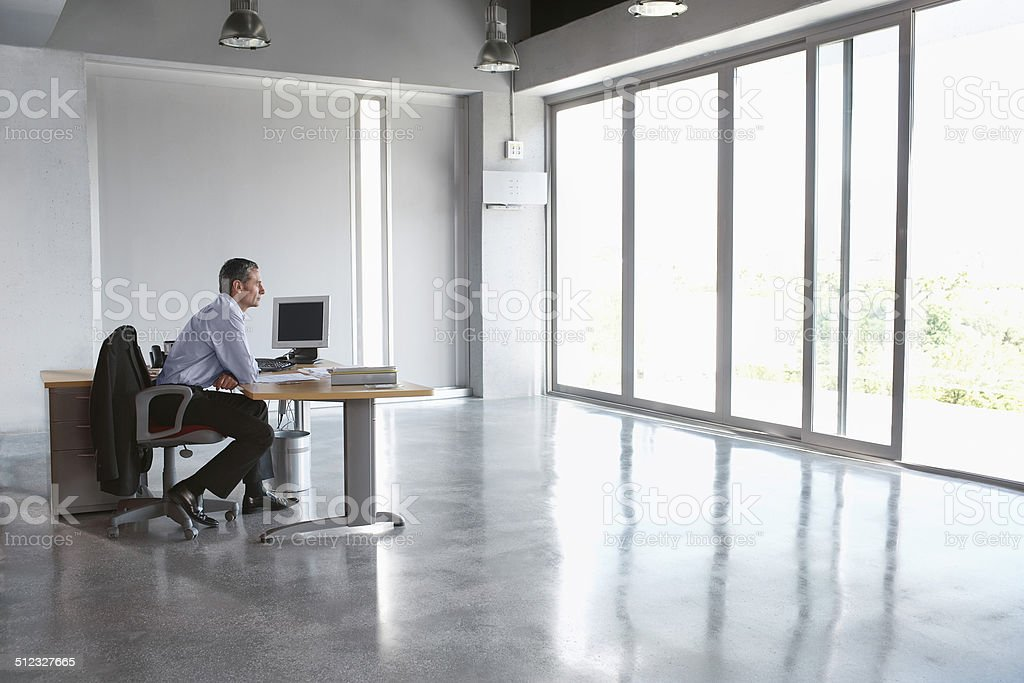 Man Sitting At Desk In Empty Office stock photo