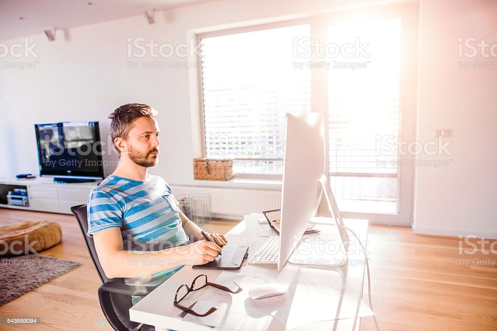 Man sitting at desk working from home on computer stock photo