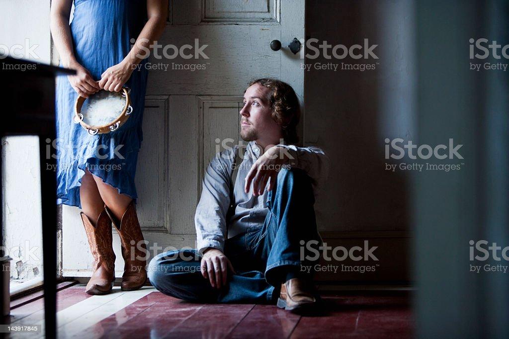 Man sitting at doorway of dark room, looking out royalty-free stock photo