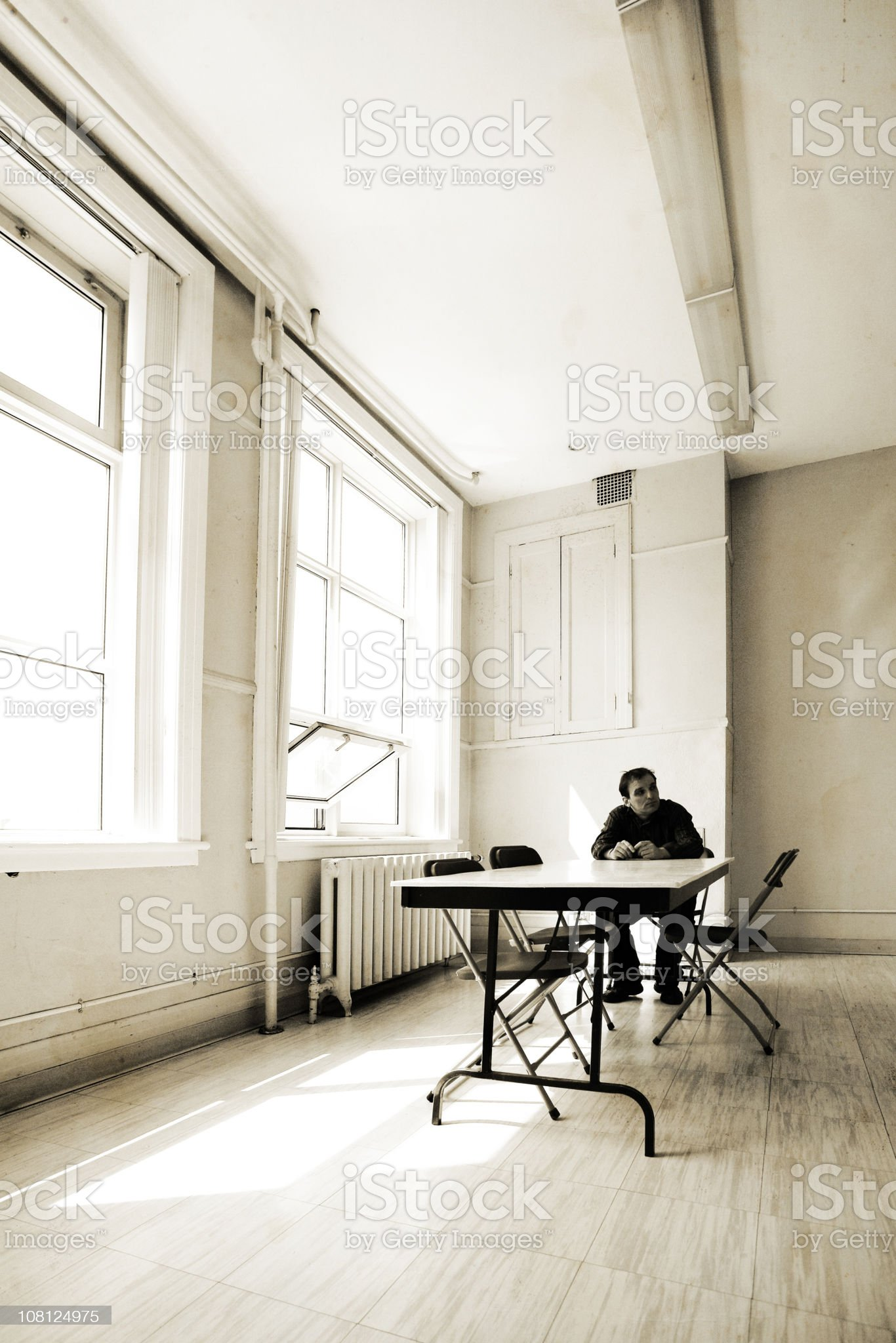 Man Sitting at Empty Table, Sepia Toned royalty-free stock photo