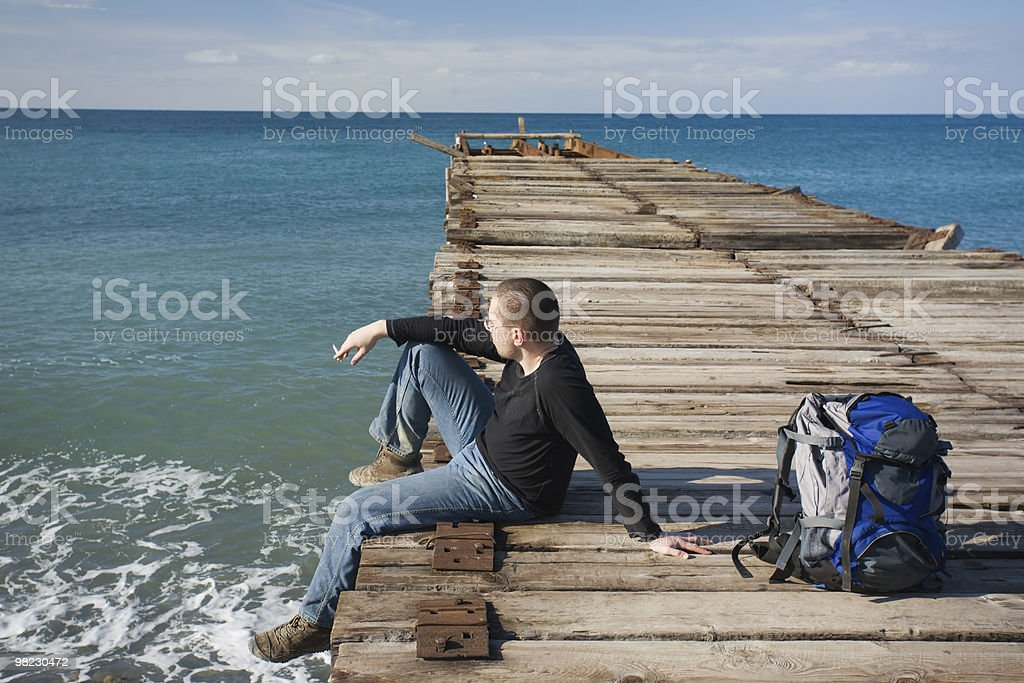 Man sitting at pier royalty-free stock photo
