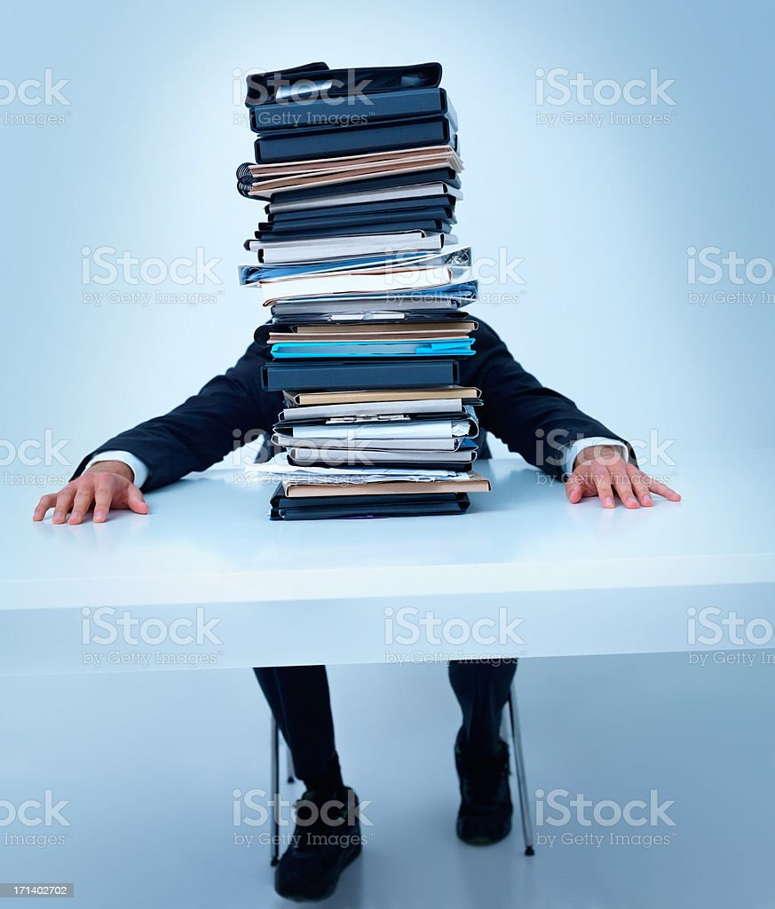 Man sitting at table with stack of files royalty-free stock photo