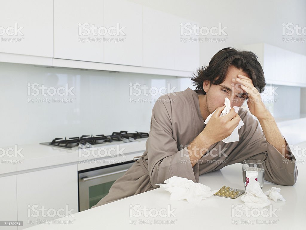 Man sitting at table with tissue blowing nose and holding head royalty-free stock photo