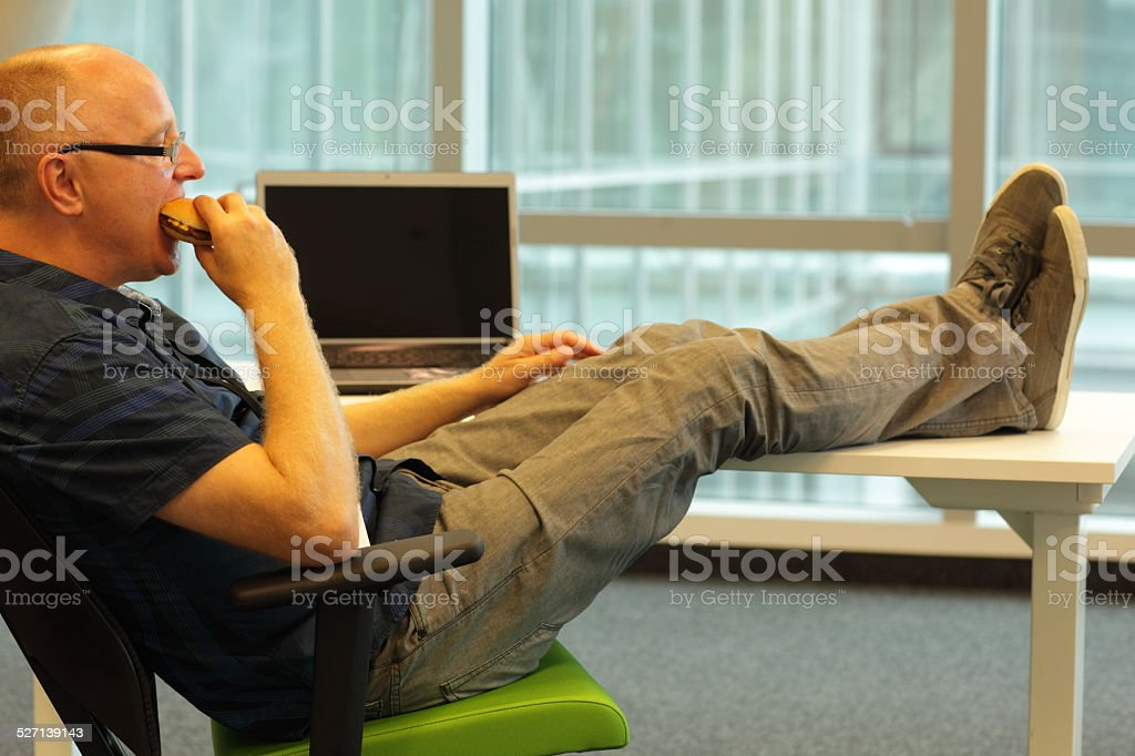 man sitting at the desk, eating hamburger in office stock photo