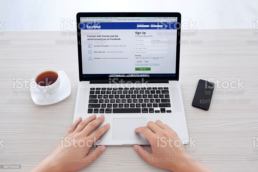 man sitting at the MacBook retina with site Facebook stock photo