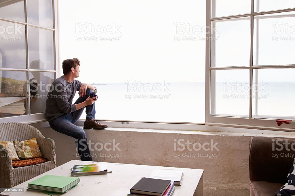 Man Sitting At Window And Looking At Beautiful Beach View stock photo