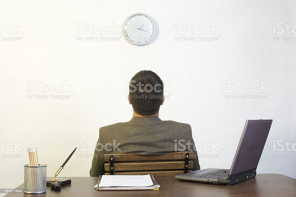 A man sitting backing against a desk looking up at a clock stock photo