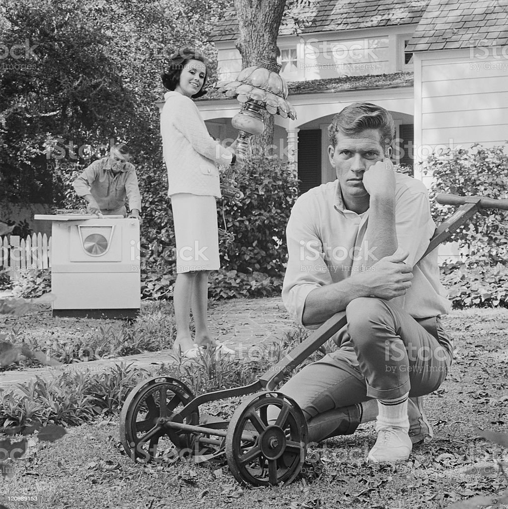 Man sitting beside mower and woman holding lamp in garden stock photo