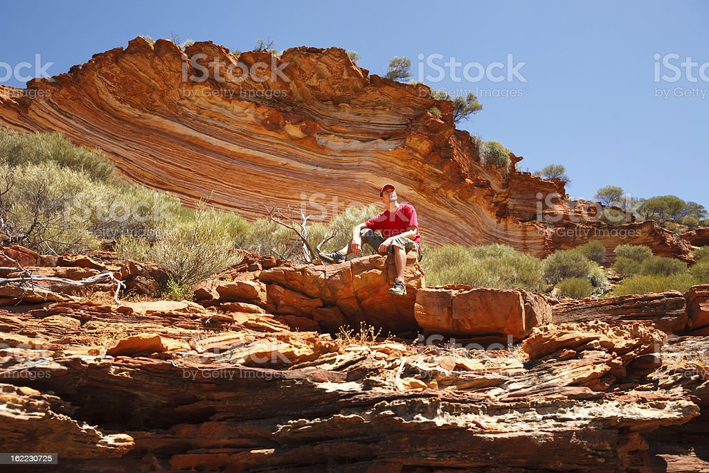 Man sitting bottom of colourful layered rock stock photo
