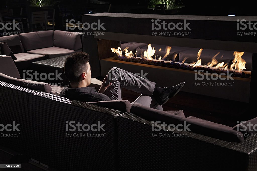 Man sitting by fireplace stock photo