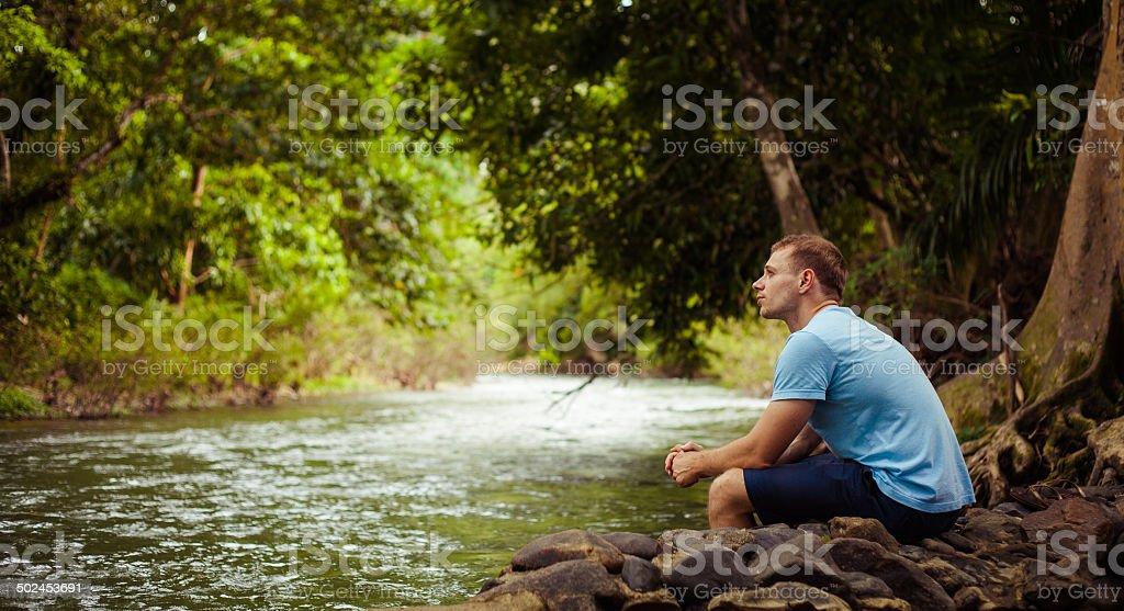Mann sitzt fallen durch Dschungel und Fluss Lizenzfreies stock-foto