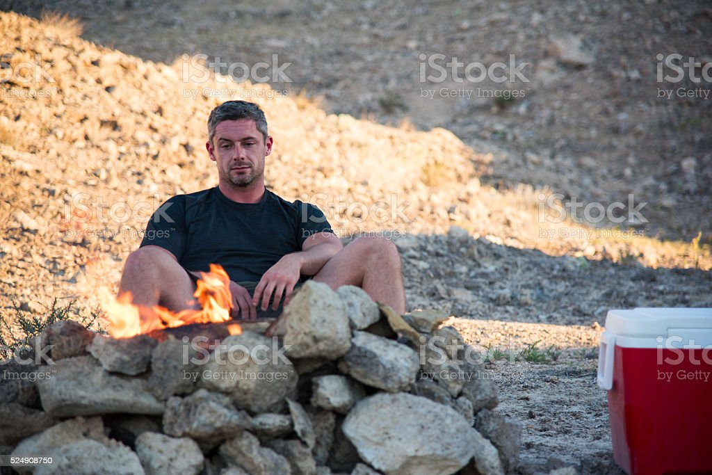 Man Sitting by the Campfire stock photo