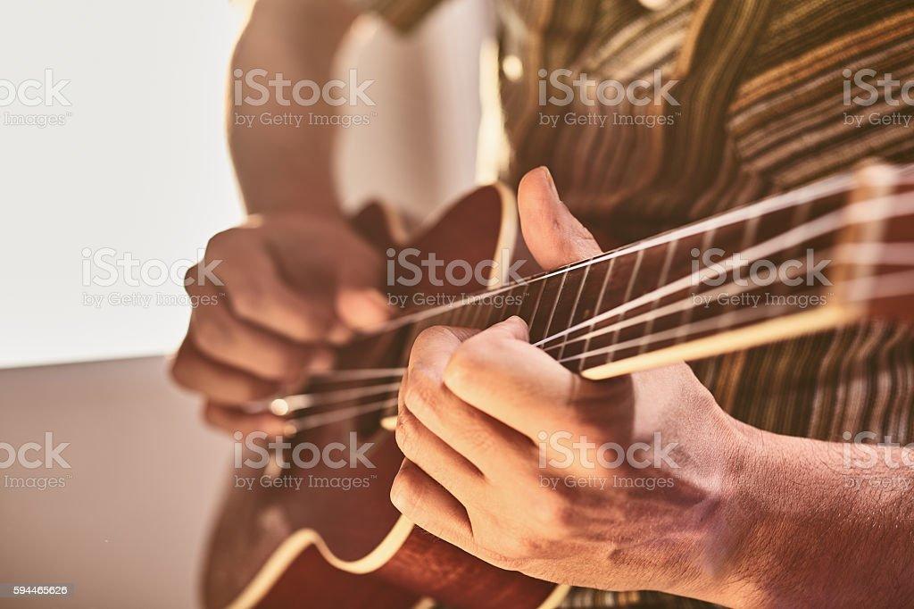 man sitting by window playing ukelele stock photo