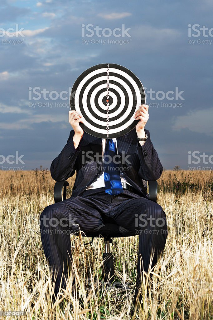 A man sitting down holding a target board up to his face royalty-free stock photo