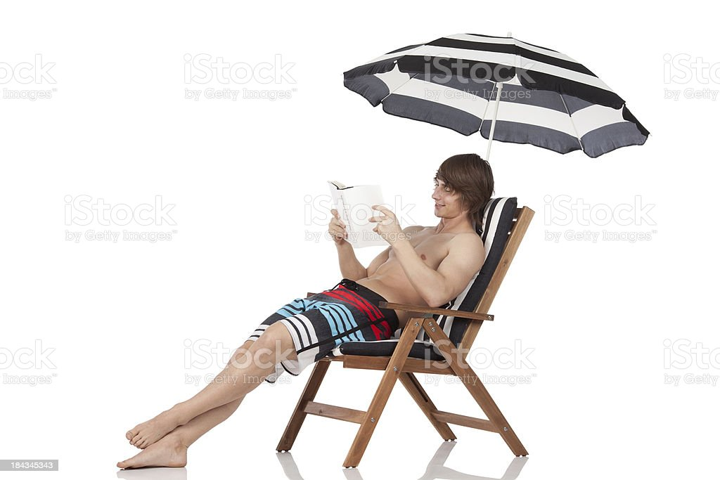 Man sitting in a deck chair reading book royalty-free stock photo