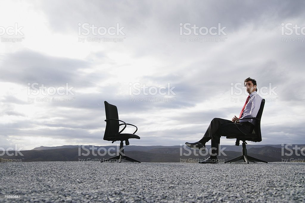 Man sitting in an office chair outdoors stock photo
